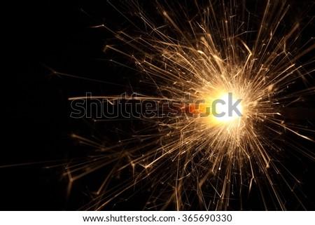 Macro photo of firework sparkler with black background. - stock photo