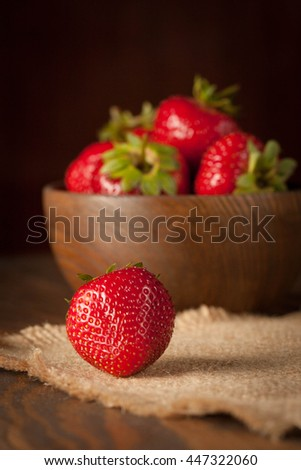 Macro photo of fresh ripe red strawberry in a wooden bowl on rustic background. Organic natural products. - stock photo