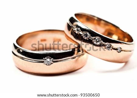 Macro photo of gold wedding rings with diamonds. White background. - stock photo