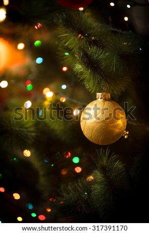 Macro photo of golden ball and light garland on Christmas tree - stock photo