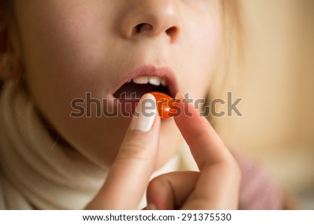 Macro photo of little sick with flu girl taking pill in mouth - stock photo