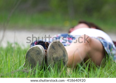 Macro photo of shoe soles. Girl resting on grass after a long physical activity  - stock photo