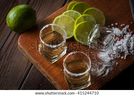 Macro photo of shots of gold Mexican tequila with lime and salt on wooden rustic background. Alcoholic drink concept. selective focus. - stock photo