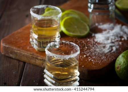 Macro photo of shots of gold Mexican tequila with lime and salt on wooden rustic background. Alcoholic drink concept. selective focus.