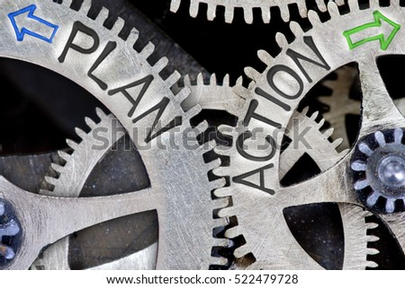 Macro photo of tooth wheel mechanism with imprinted arrows and PLAN, ACTION concept words