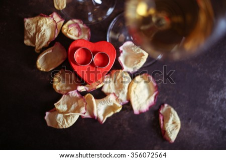 Macro photo of two classical simple wedding rings in box in the form of red hearts. Celebrating Valentine's Day, a marriage proposal. - stock photo