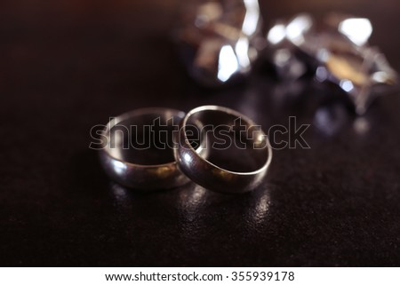 Macro photo of two classical simple wedding rings on the black background, a marriage proposal. - stock photo