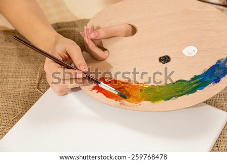 Macro photo of young female artist dipping paintbrush in paint on pallet - stock photo