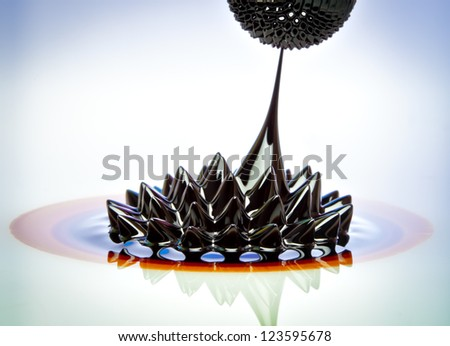 Macro photograph of Ferrofluid flowing from one magnet to another. Ferrofluid is a colloidal liquid of nanoscale particles in a carrier fluid that becomes magnetized by approaching a magnet. - stock photo
