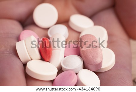 Macro photograph of various colorful medicinal pills - holding pills in the hand - stock photo