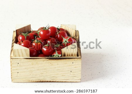 macro photographed in daylight red tomatoes in wooden crate
