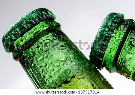 macro photography of two bottles of beer on white background - stock photo