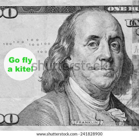 "Macro portrait of Benjamin Franklin from hundred-dollar U.S. bill with word balloon: ""Go fly a kite!"" (in black and white, except for green text; some identifiers have been removed) - stock photo"