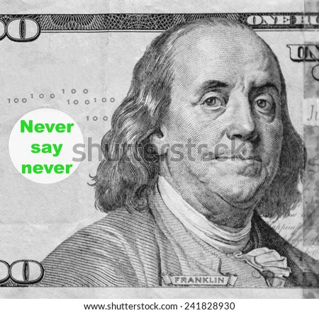 "Macro portrait of Benjamin Franklin from hundred-dollar U.S. bill with word balloon: ""Never say never"" (in black and white, except for green text; some identifiers have been removed) - stock photo"
