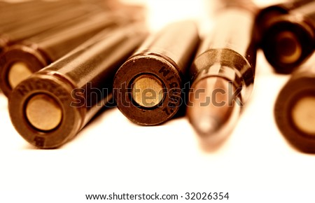 Macro set of Kalashnikov AK-47 (7,62 mm) cartridges (shallow DOF) on white background. Live ammunition for automatic weapon closeup toned image selective focus.