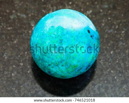 macro shooting of natural mineral rock specimen - ball from Chrysocolla gemstone on dark granite background