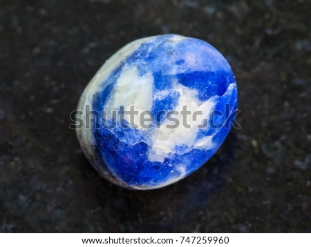macro shooting of natural mineral rock specimen - polished Sodalite gem stone on dark granite background
