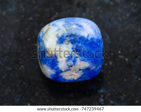 macro shooting of natural mineral rock specimen - polished Sodalite gemstone on dark granite background