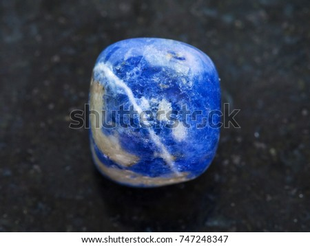 macro shooting of natural mineral rock specimen - tumbled Sodalite gemstone on dark granite background
