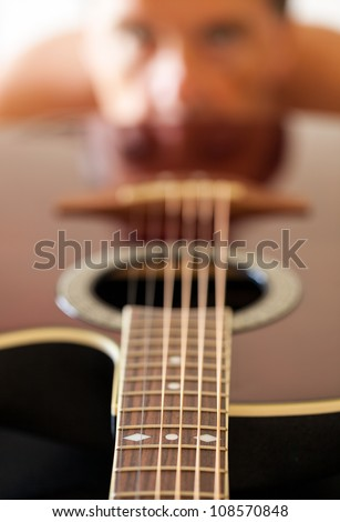Macro shot down the fretboard of acoustic guitar with shallow depth of field with guitarist face in the distance reflected