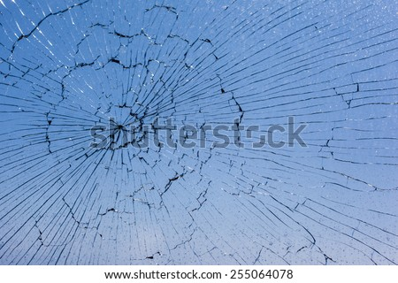 macro shot of a broken glass window against the blue sky - stock photo