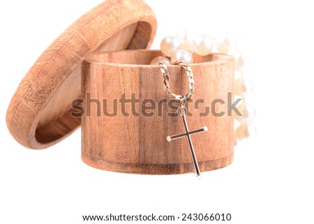 Macro shot of a christian crucifix and pearls in a wooden box - stock photo