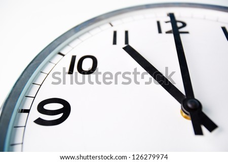 Macro shot of a clock face showing eleven o'??clock - stock photo
