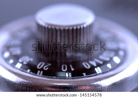 Macro shot of a combination safe lock button, soft focus, blue tone - stock photo