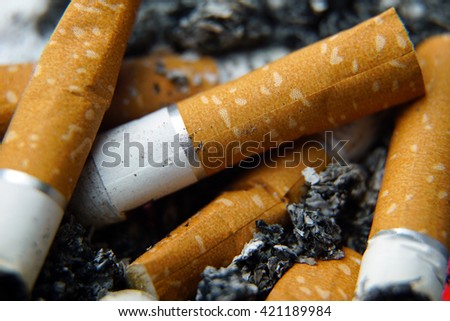 Macro shot of a group of cigarette butts and ash in an ashtray. - stock photo