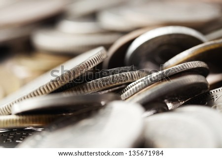 Macro shot of a large quantity of unrecognizable coins stacked in chaos. Very shallow depth of field. - stock photo