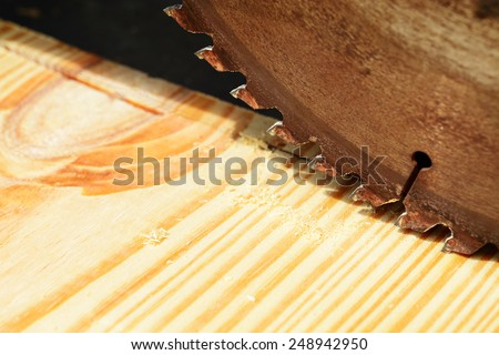 Macro shot of a table saw blade over a pine wood board - stock photo