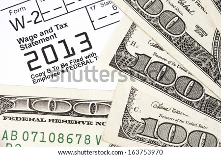 Macro shot of a W2 form with money around it. - stock photo