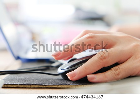 Macro shot of a woman hand using a computer mouse.
