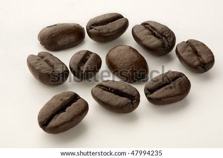 Macro shot of Arabica coffee beans isolated on white - stock photo