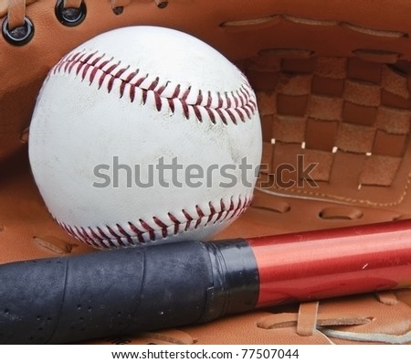 Macro shot of baseball in glove with bat and shallow depth of field for attention on ball and bat