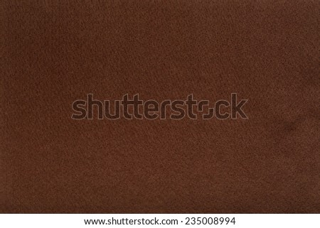 Macro shot of brown felt tissue cloth, closeup texture background with details in structure.