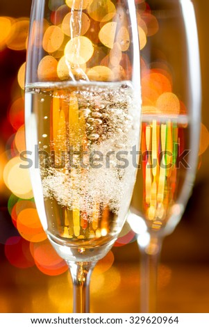 Macro shot of bubbles of Champagne against sparkling lights - stock photo