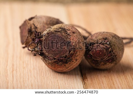 Macro shot of freshly harvested beets from an organic farm on cedar wooden planks - three - stock photo