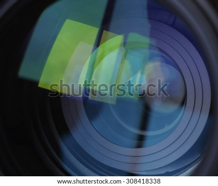 Macro shot of front element of a lens with beautiful color lights reflections - stock photo