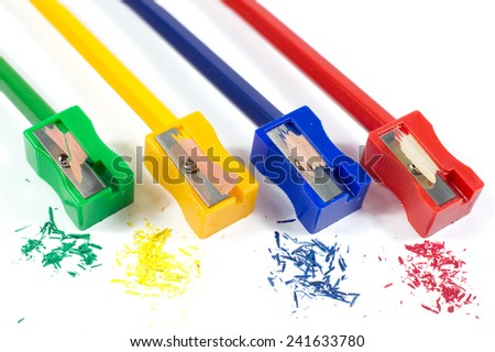 Macro Shot of Green, Yellow, Blue and Red  Pencil Sharpeners Sharpening Pencils with Colorful Pencil Shavings Isolated on White Background  - stock photo