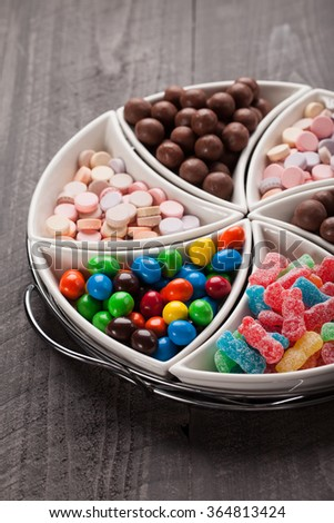 Macro shot of large container with separated assortments of colorful candy