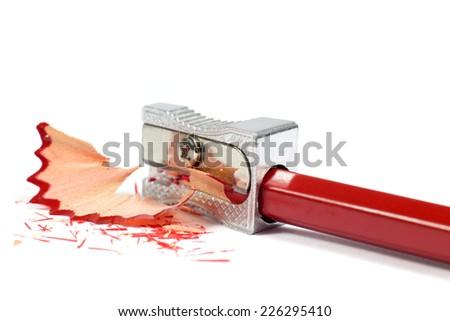 Macro Shot of Metallic Pencil Sharpener Sharpening Red Pencil Isolated on White Background - stock photo