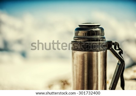 Macro shot of old shabby marching thermos in winter in snow and with blured snow-capped mountains on background