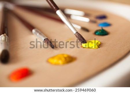 Macro shot of paintbrush dipped in yellow oil paint from pallet - stock photo