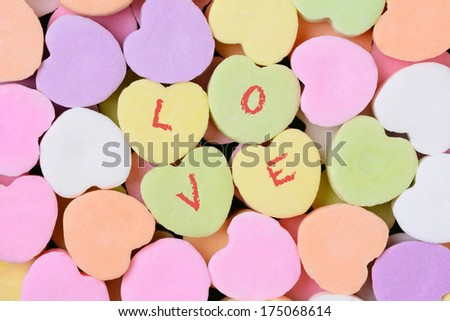 Macro shot of pastel candy hearts for Valentine's Day. Four of the candies have the word LOVE spelled out in individual letters.  - stock photo