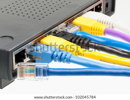 Macro shot of plugs on cat5e cables of many colors isolated against white background plugged into router