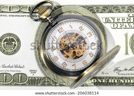 Macro shot of pocket watch face with 100 dollar bill Ben Franklin - stock photo