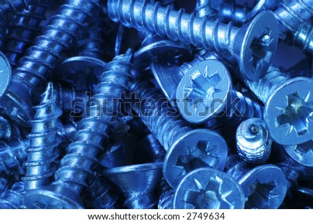 Macro shot of small crosspoint screws, with a cold tone. - stock photo