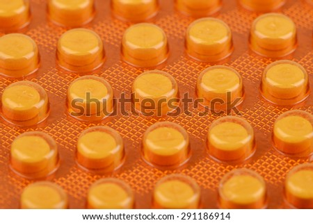 Macro shot of small pills in yellow package - stock photo