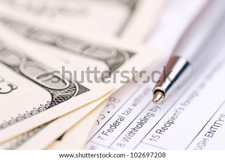 Macro shot of the pen with american hundred-dollar bills and tax form - stock photo
